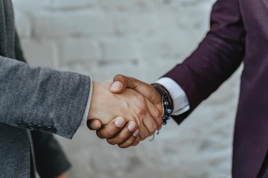 Мужчины в деловых костюмах пожимают друг другу руки