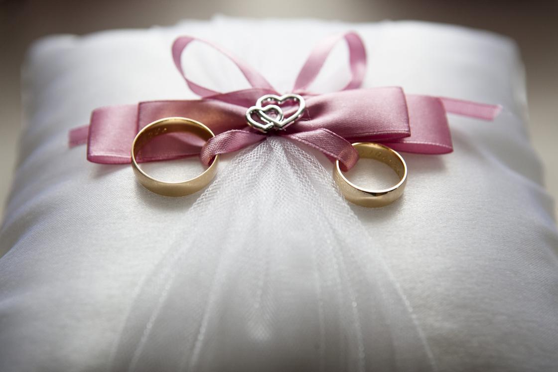 Обручальные кольца на белой подушечке с розовым бантом