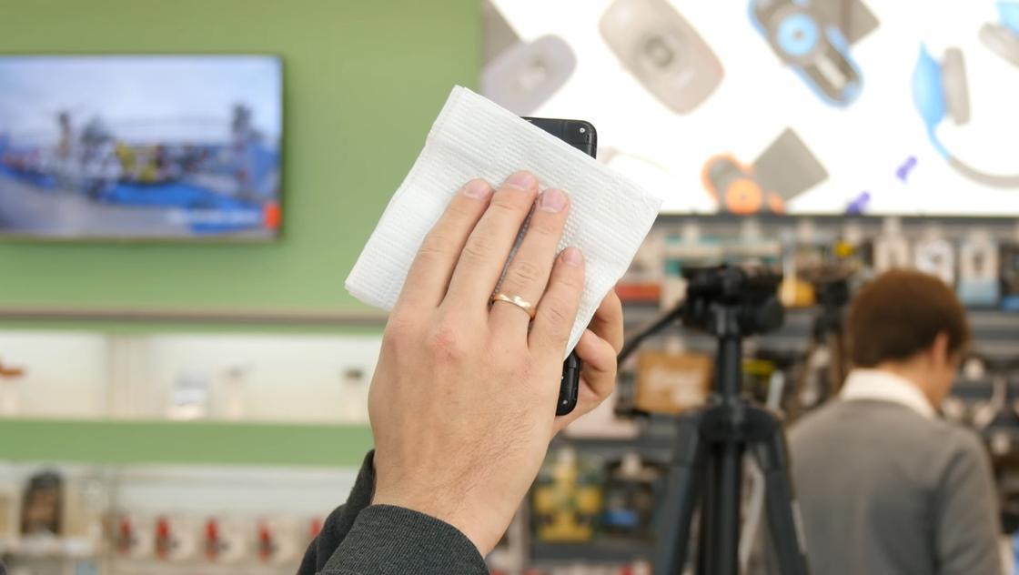 Вытирают телефон салфеткой