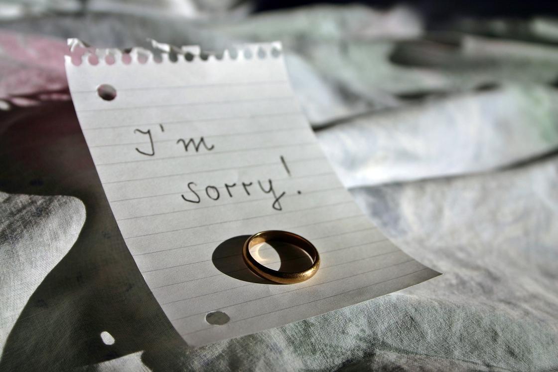 Обручальное кольцо на листке с предложением «Прости!»