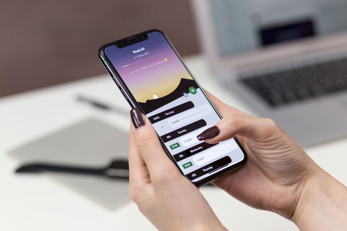 Девушка держит в руках смартфон с включенным дисплеем