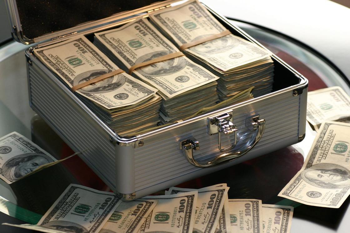 Чемоданчик с долларами на стеклянном столе