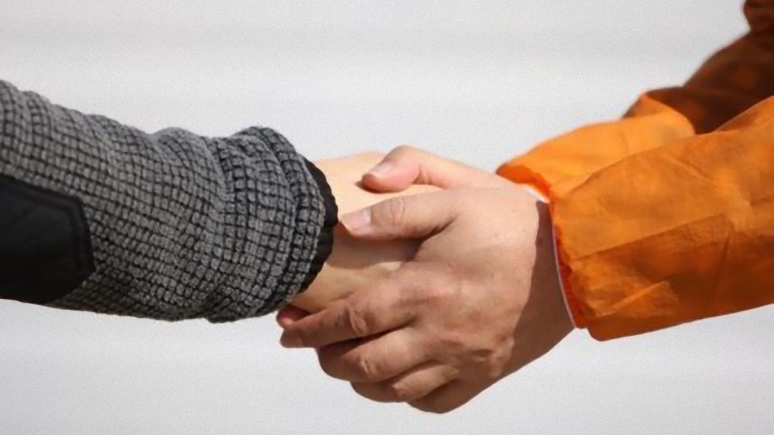 Руку пожимают двумя руками