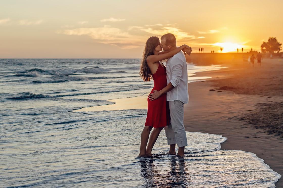 Мужчина и женщина в красном платье целуются в прибое на фоне заката
