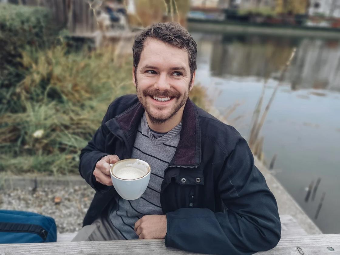 Мужчина с чашкой на фоне реки