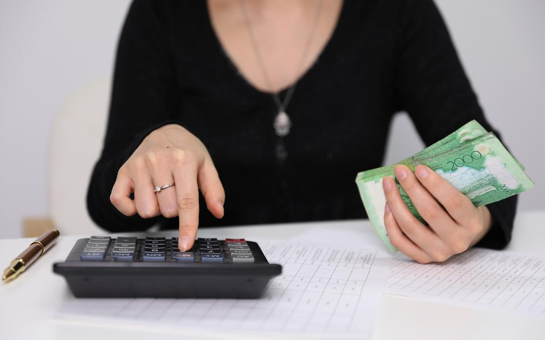 Женщина с калькулятором и деньгами
