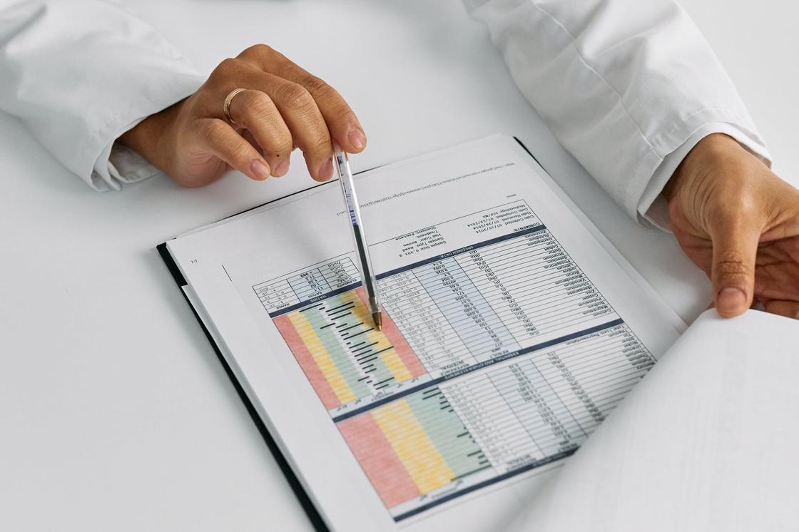 Врач указывает ручкой на строку в таблице