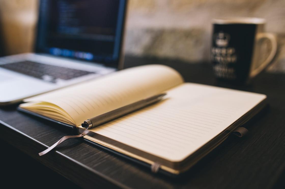 Блокнот с ручкой, ноутбук и чайная чашка на деревянном столе
