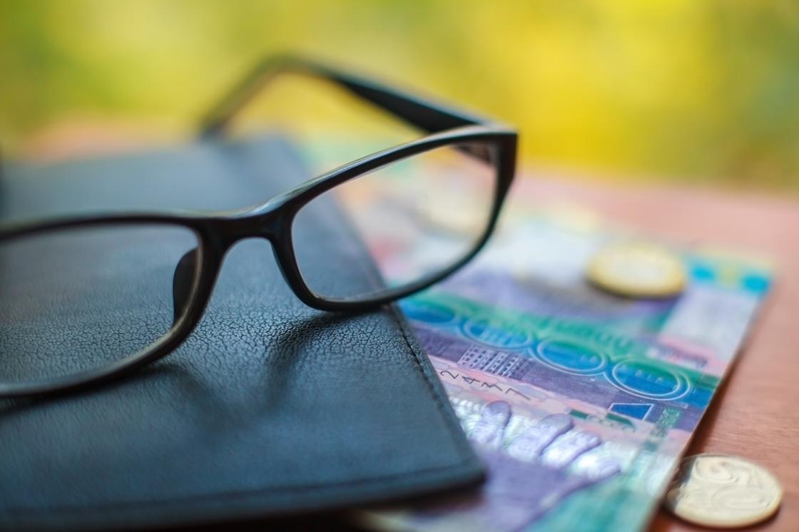 Очки лежат на кожаной папке и деньгах