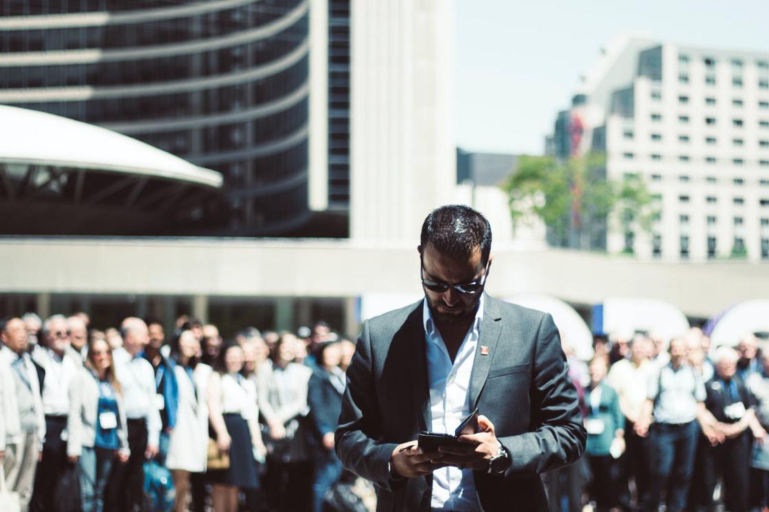 Мужчина смотрит в телефон на фоне стоящих недалеко людей