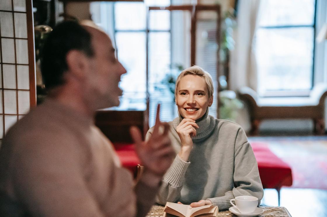 Женщина с книгой в руках слушает мужчину и улыбается