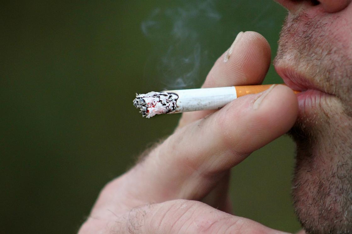 Мужчина держит сигарету двумя пальцами и затягивается
