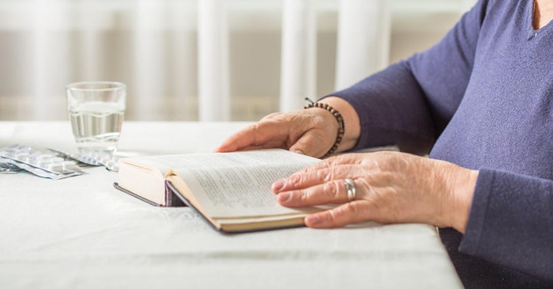 Женщина читает книгу, рядом стакан воды и лекарства