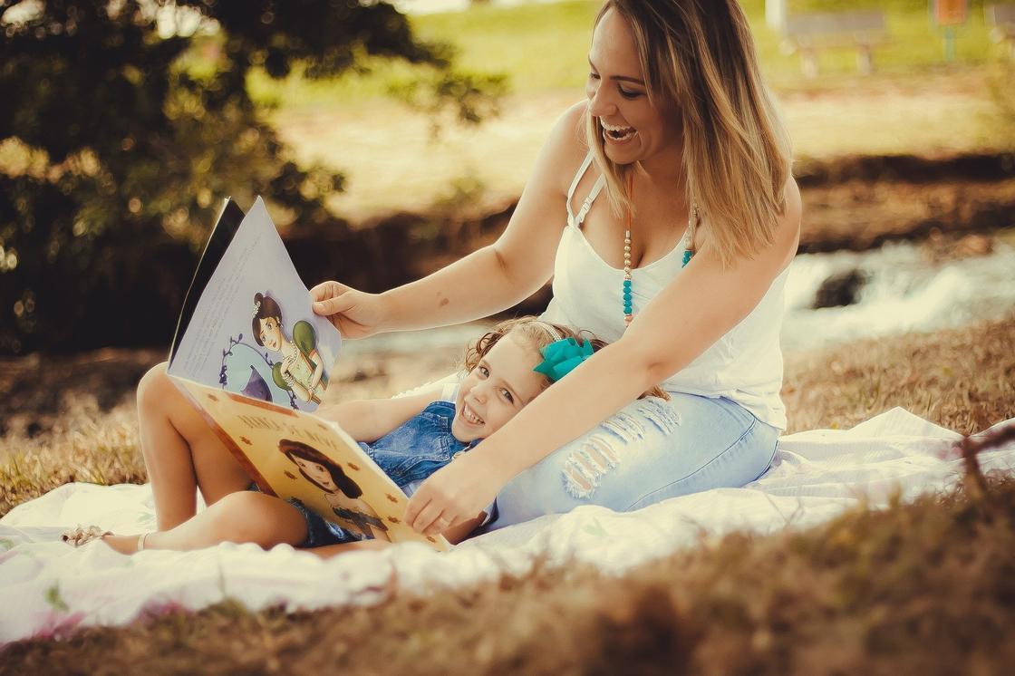 Женщина и девочка смотрят книгу