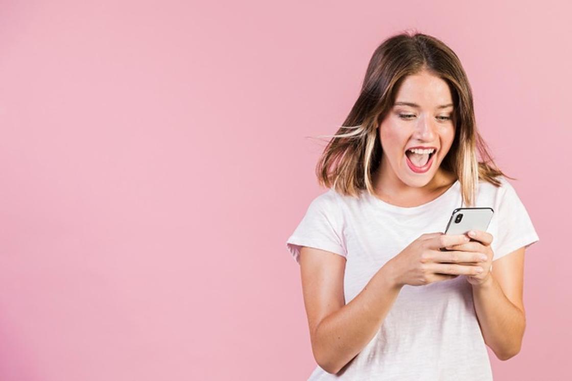 Девушка удивленно смотрит в телефон