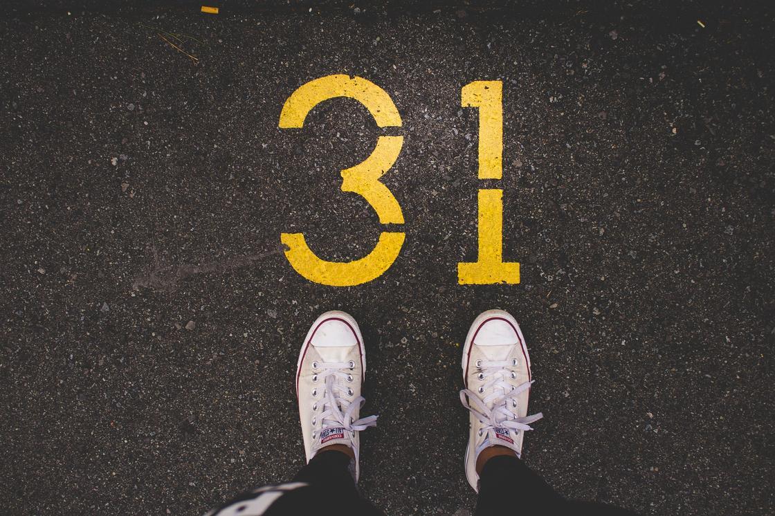 Число 31 на асфальте и ноги в кедах