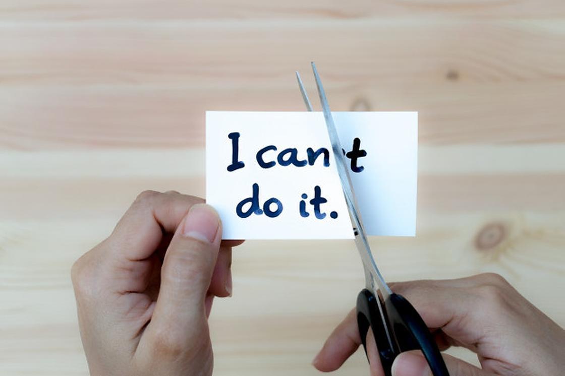 Ножницы в руках разрезают лист с надписью I can't do it