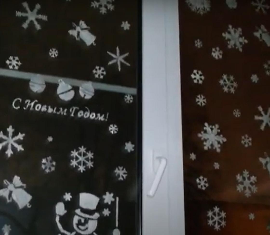 Украшенное новогодними рисунками и надписью окно