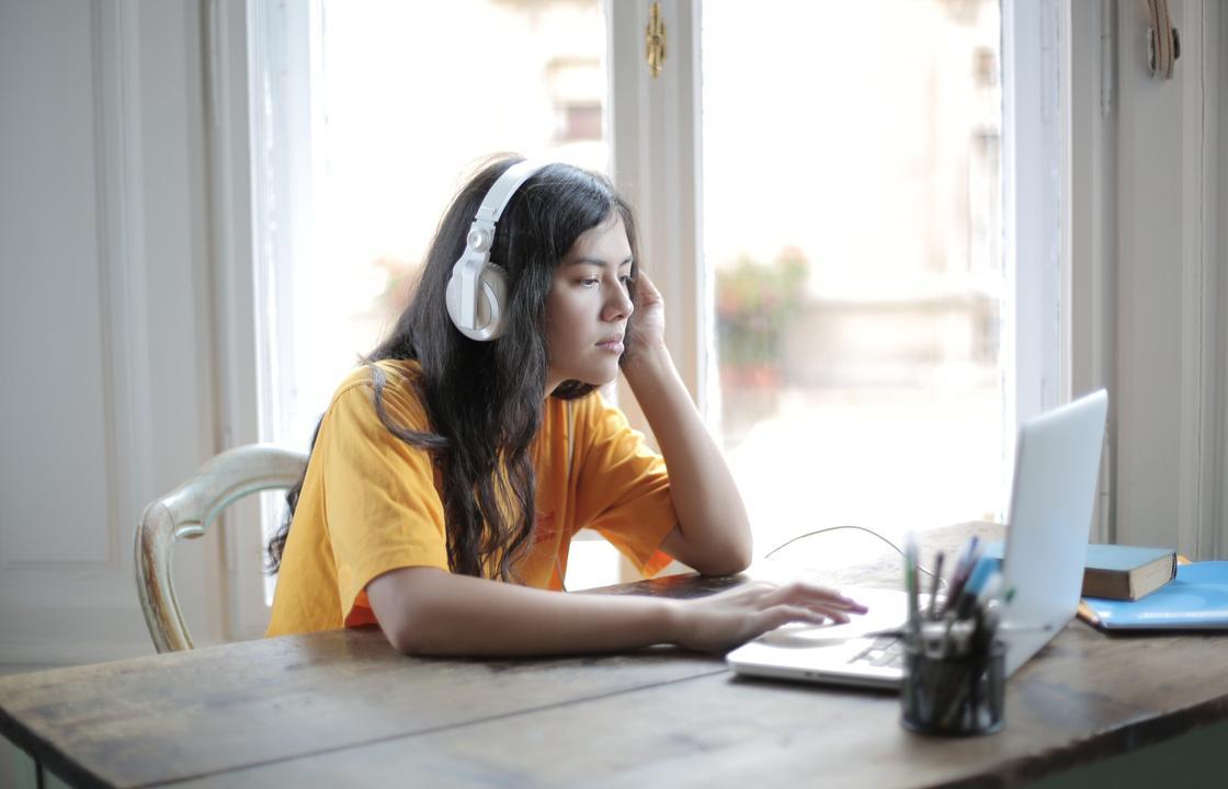 Девушка в наушниках за ноутбуком