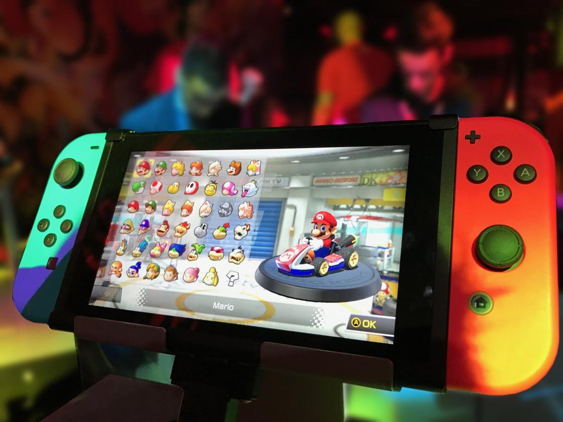 """Игра """"Супер Марио"""" на экране телефона с игровой консолью"""