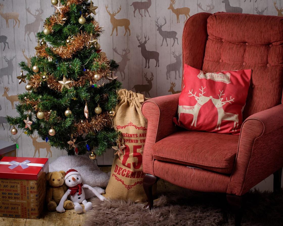 Подушка с оленями на кресле у наряженной елки