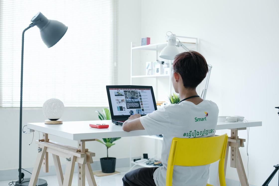 Молодой человек сидит за рабочим столом и смотрит в ноутбук