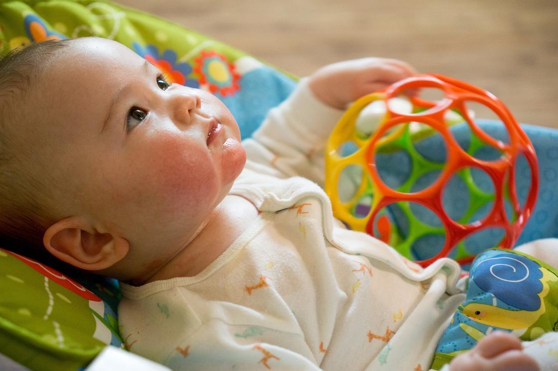 Младенец играет с игрушками
