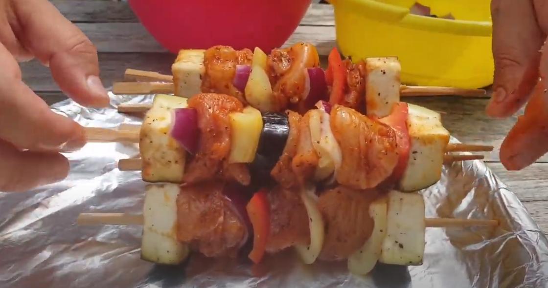 На столе шашлык из курицы с овощами