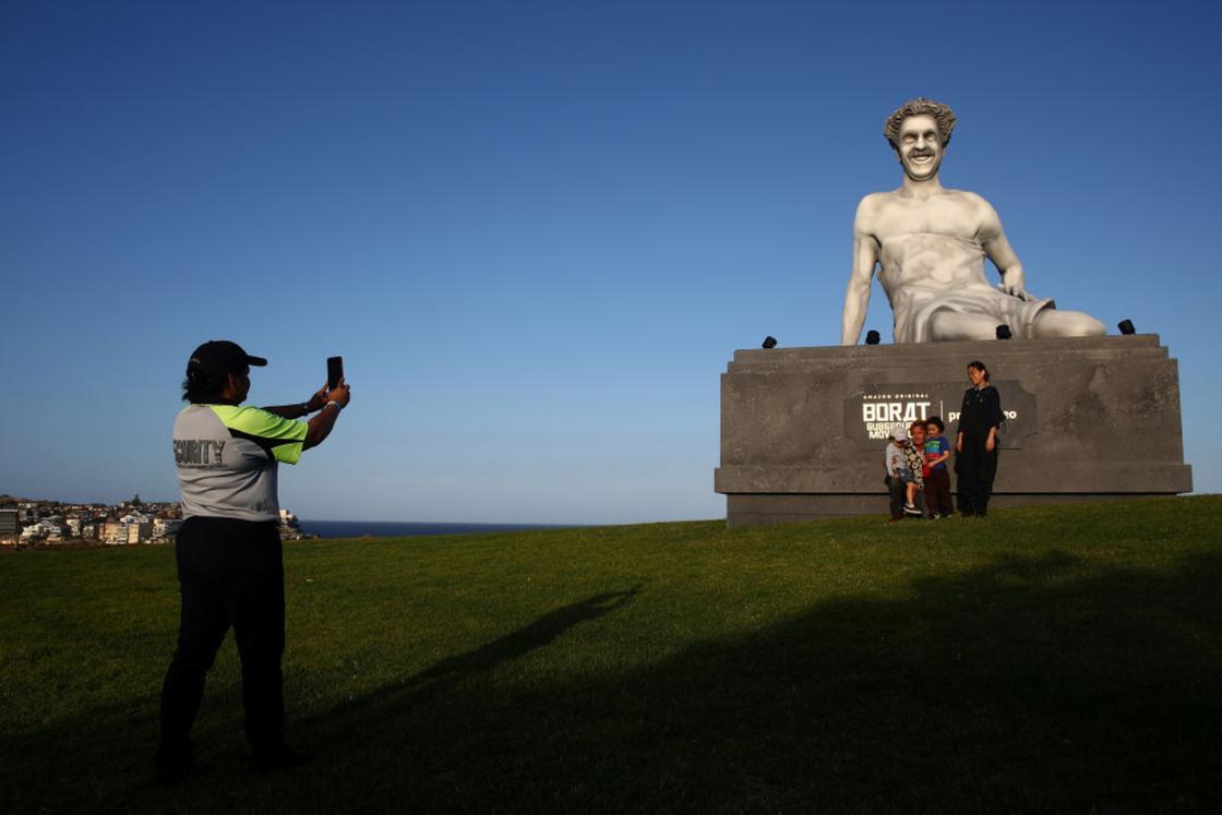 Люди фотографируются возле статуи Бората