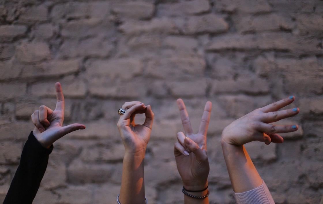 Люди составили из пальцев рук слово «любовь»