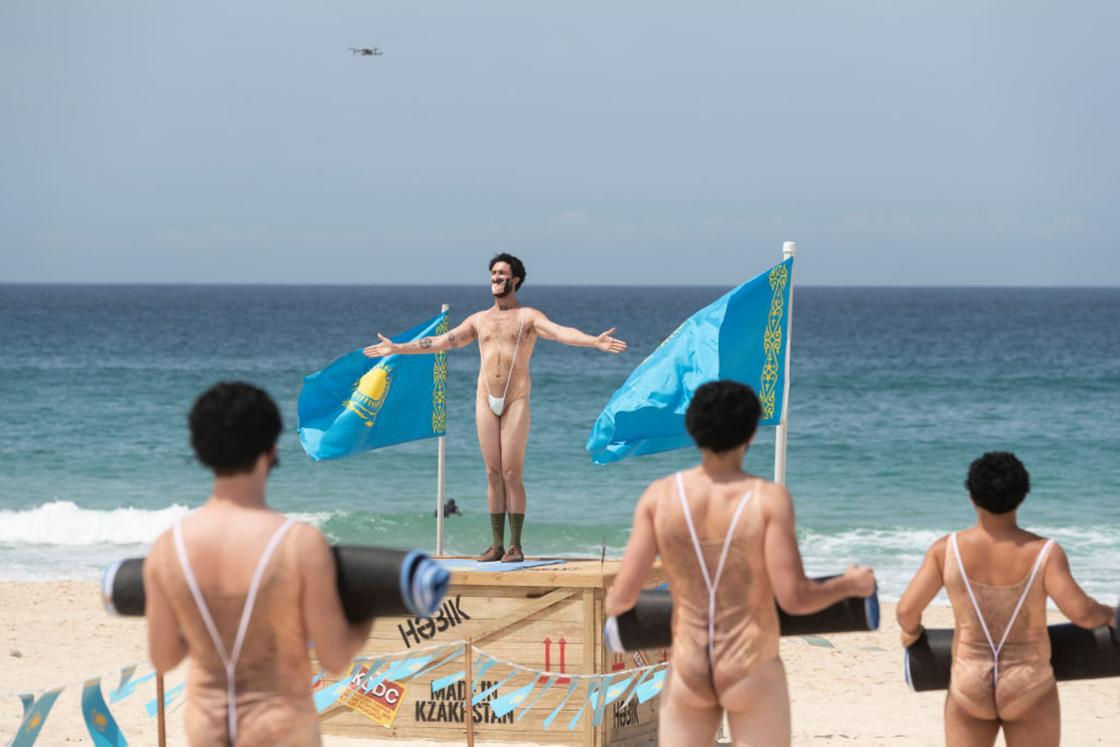 """Люди в """"костюмах"""" Бората стоят на пляже"""