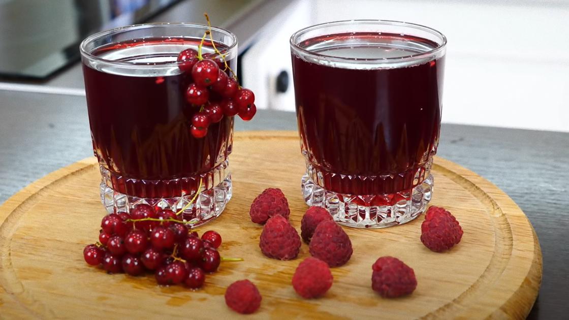 Красный компот в стаканах и ягоды на столе