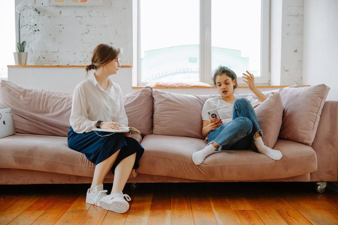 Женщина и девочка-подросток сидят на диване на фоне окна