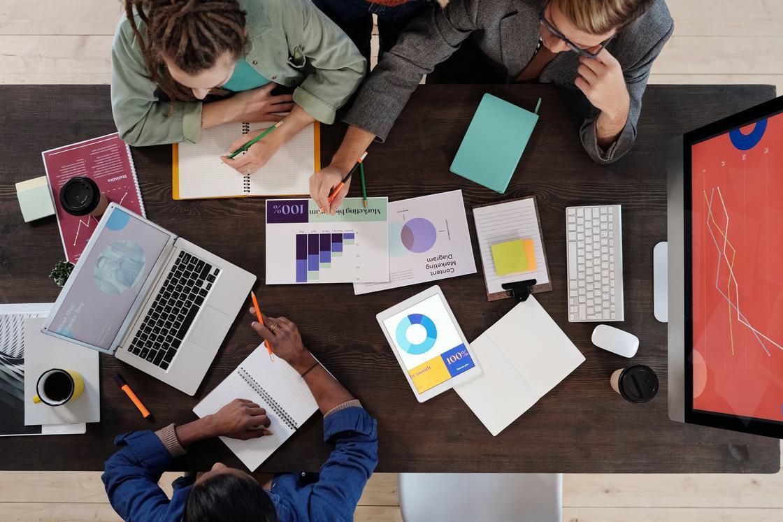 Трое людей обсуждают проекты, сидя за рабочим столом с ноутбуками