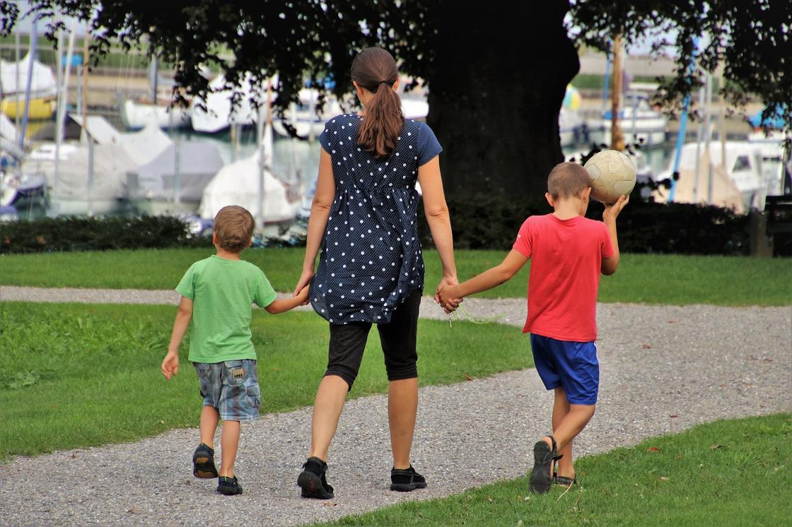 Женщина ведет за руки детей