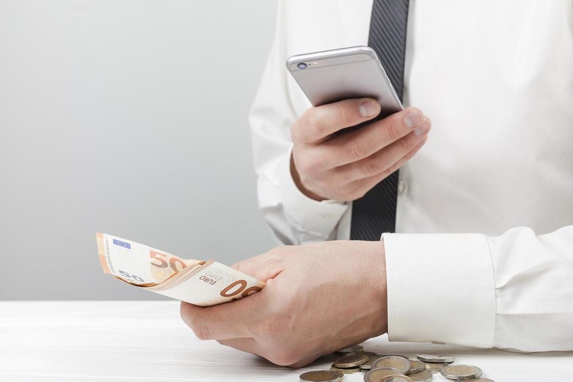 Мужчина держит деньги и смартфон