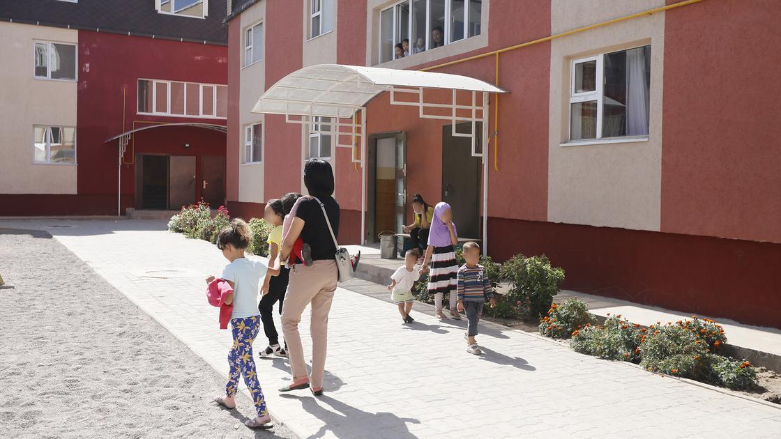 Женщина с детьми идет возле дома