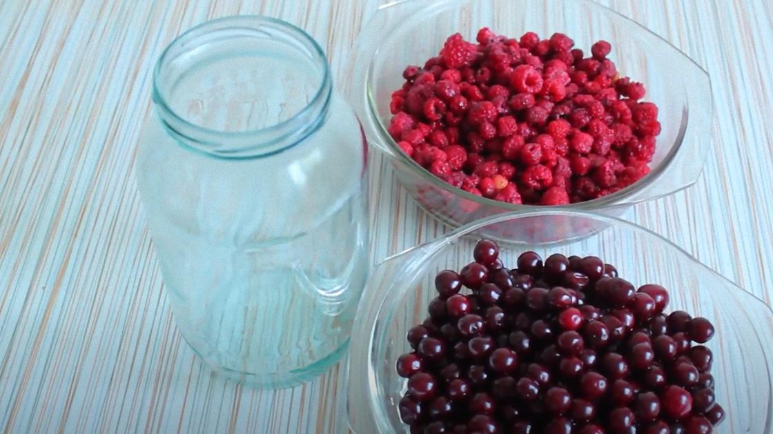 Пустая банка, вишни и малина в мисках