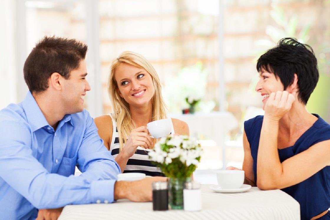 Девушка с парнем и женщиной за столом