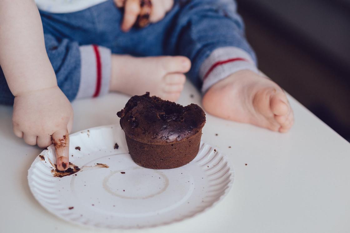 Маленький ребенок, выпачканный шоколадом, и тарелка с шоколадным кексом