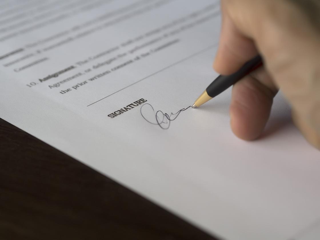 Человек ставит подпись в докуенте