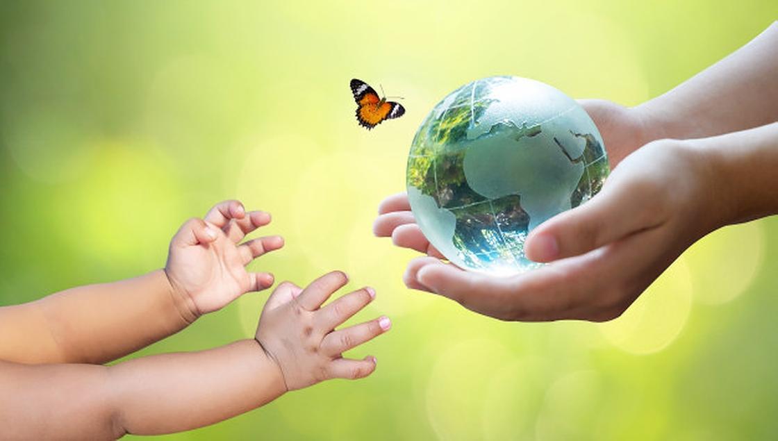 Руки взрослого передают земной шар ребенку
