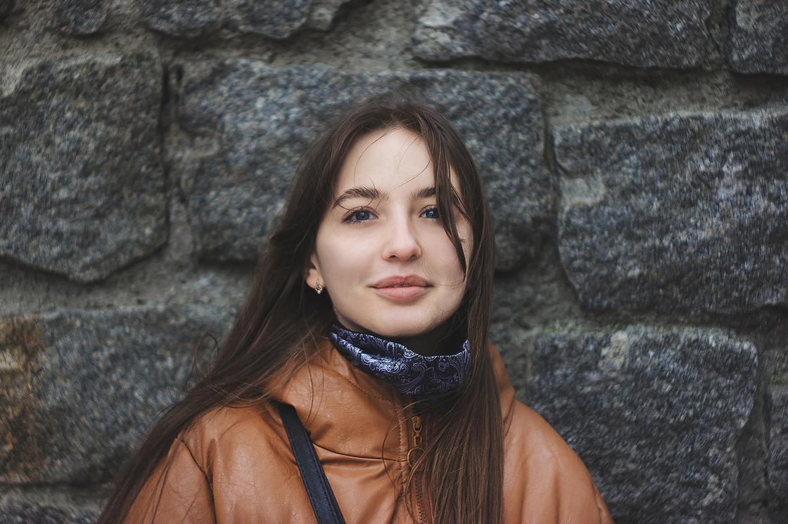 Девушка на фоне каменной стены