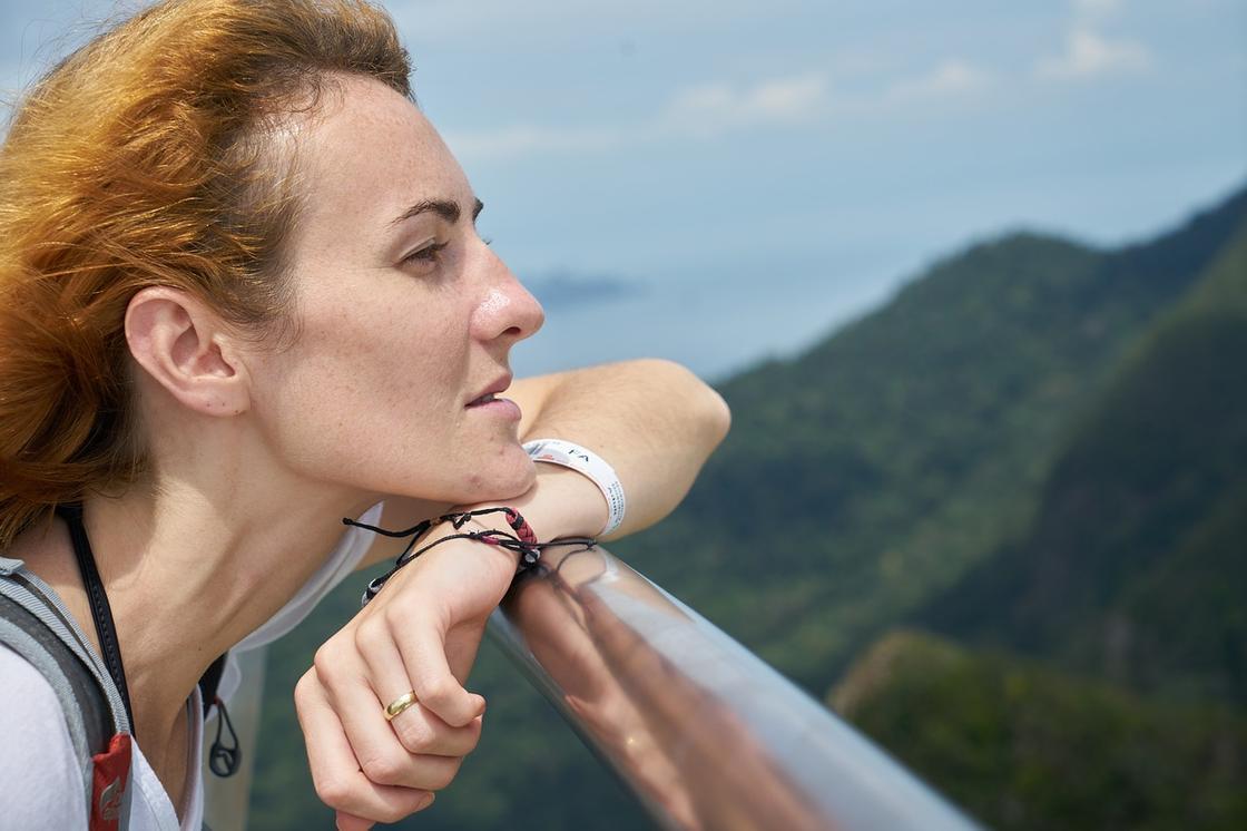 Девушка у поручней смотрит на горы