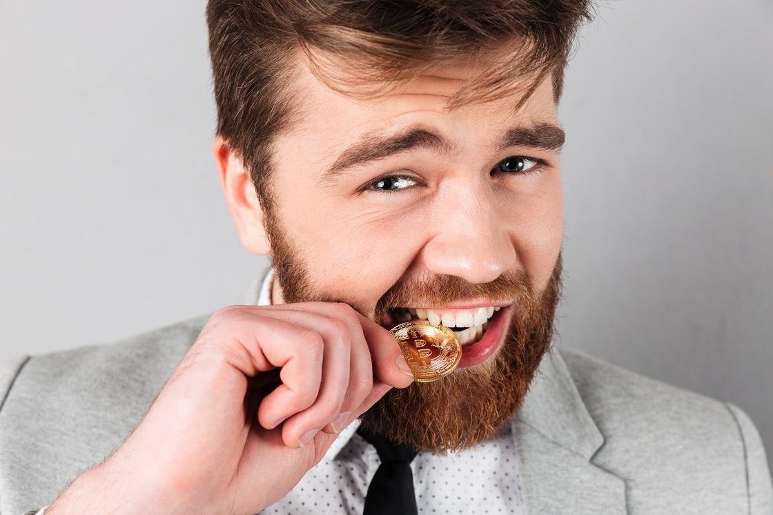 Мужчина кусает золотую монету