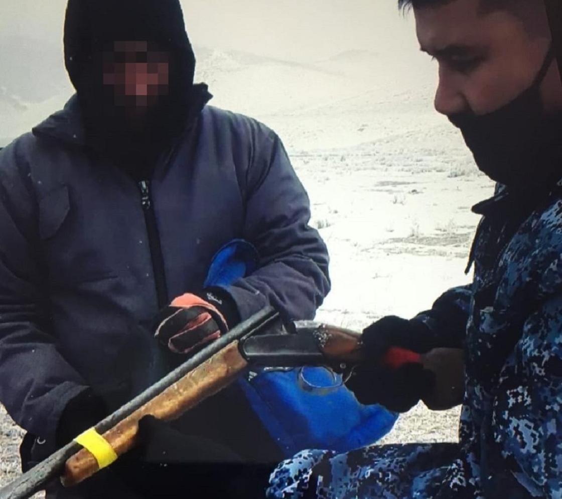 Инспектор полиции изымает ружье у мужчины