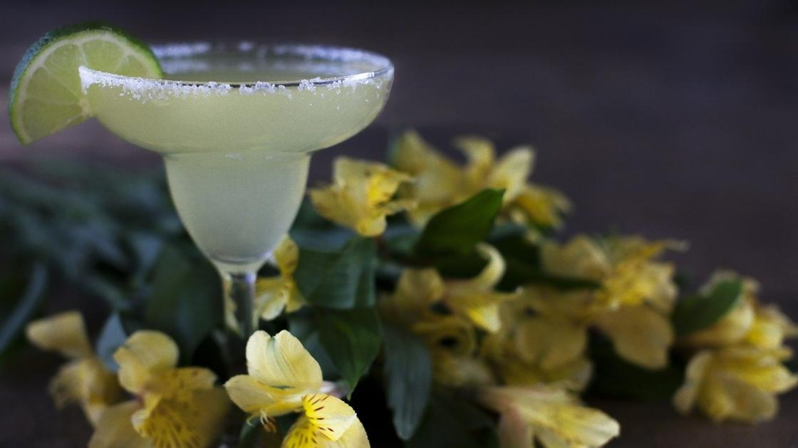 Бокал с коктейлем и кусочком лайма, цветы