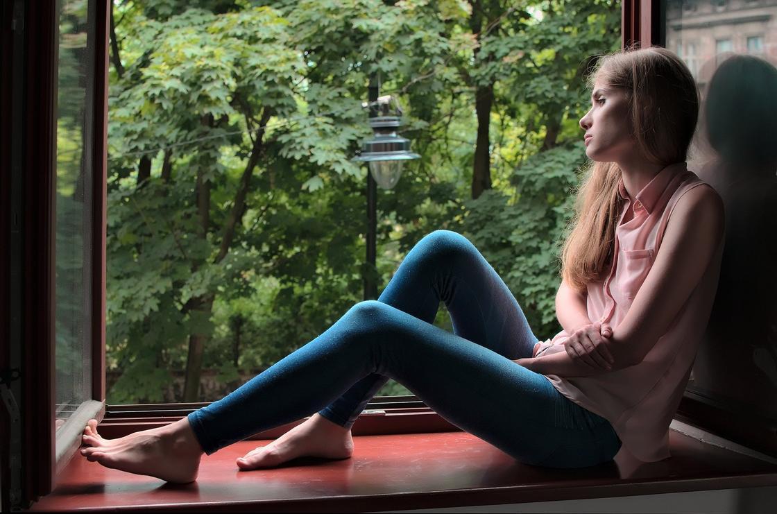 Печальная девушка сидит на подоконнике