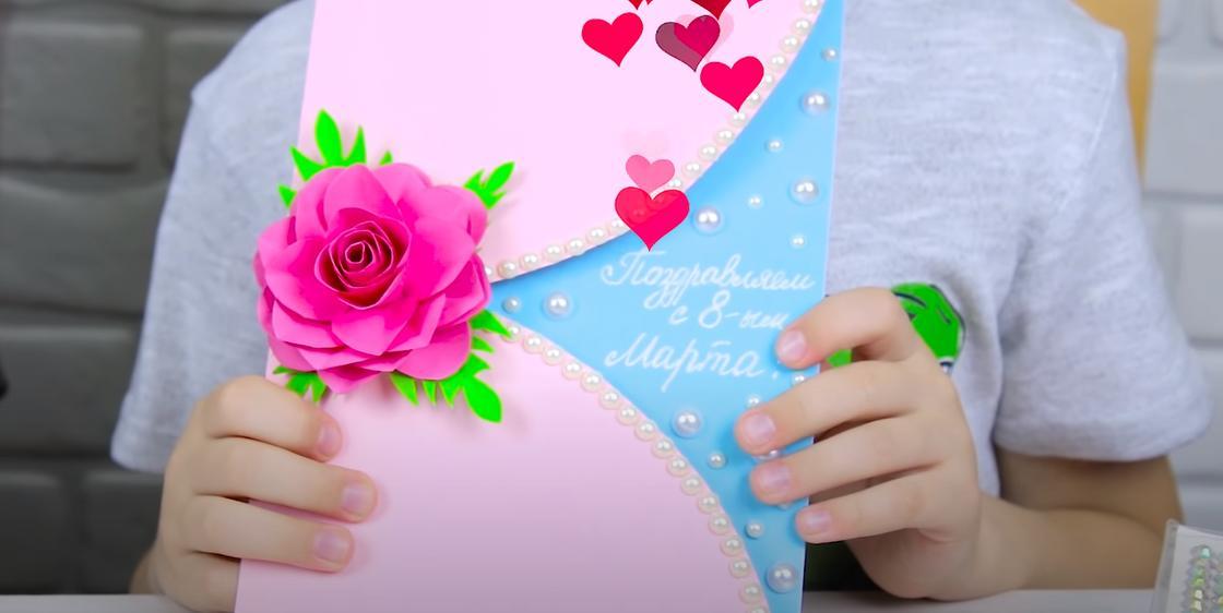 Мальчик держит открытку с 8 Марта
