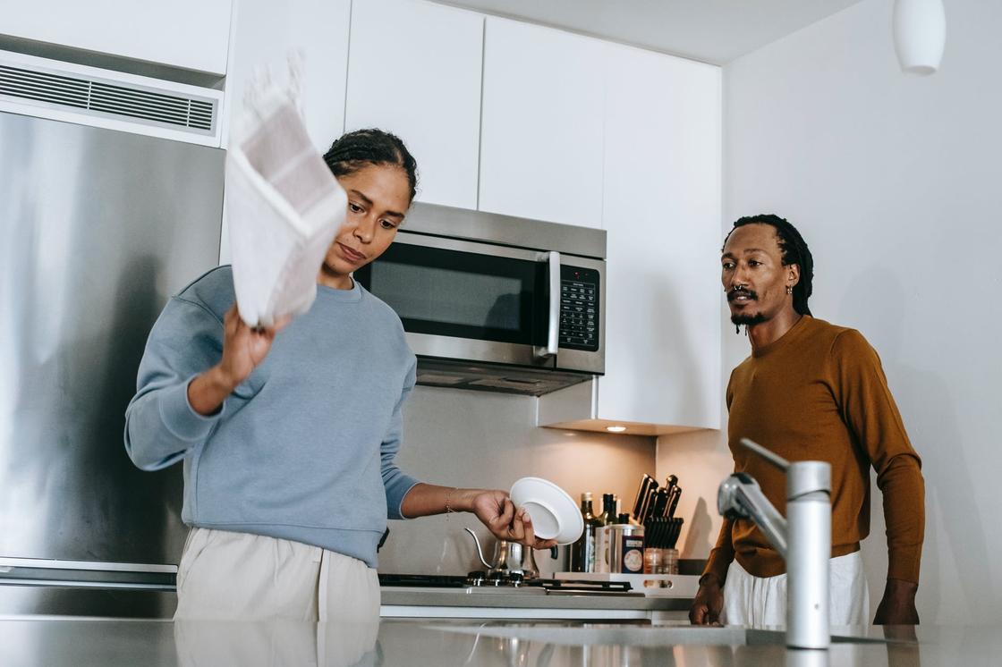 Женщина с недовольным лицом стоит на кухне рядом с мужчиной